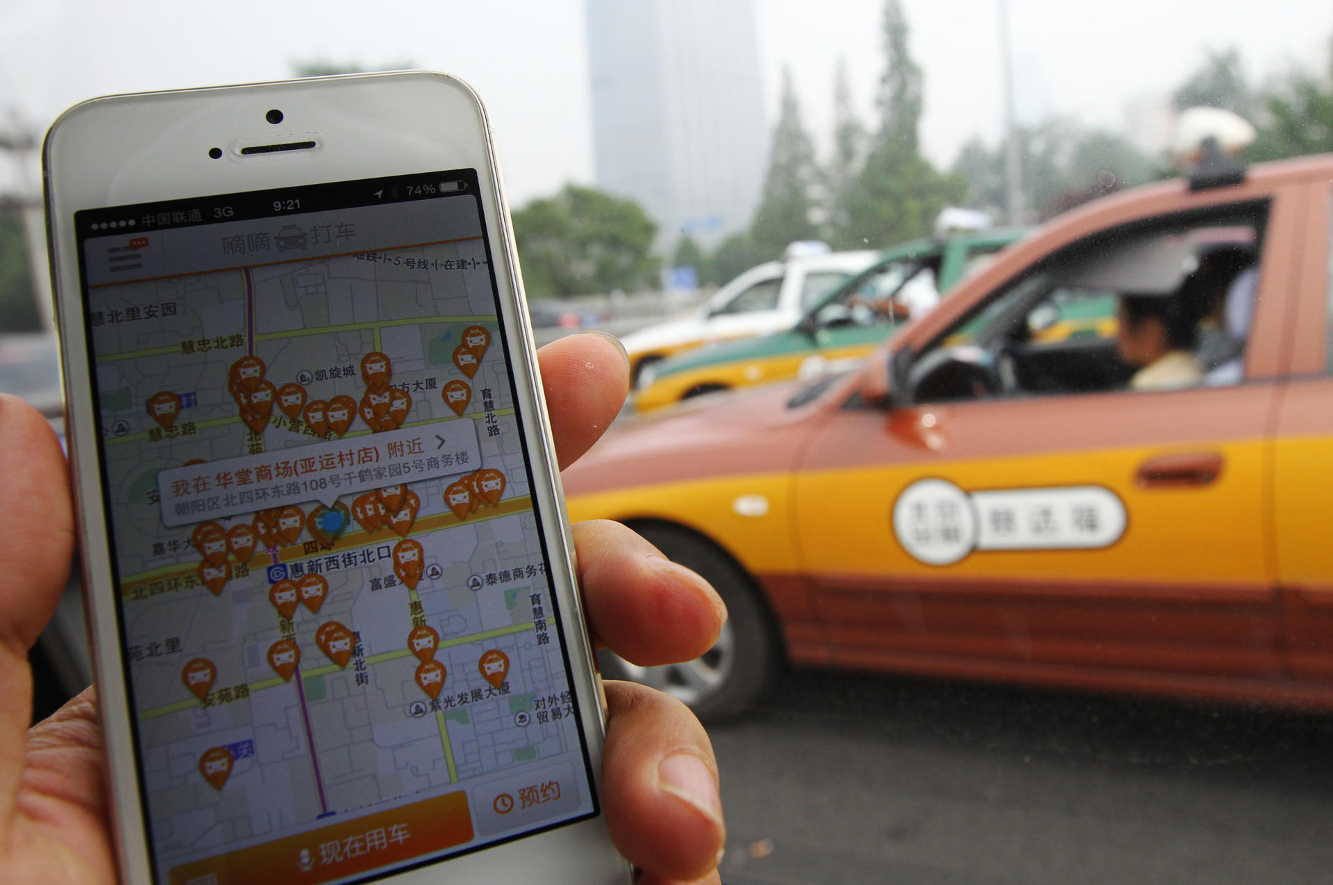 The screen of mobile phone shows the Didi Dache app is pictured with a taxi passes by   in Beijing on Jun 19, 2014. Didi Dache has become China's most popular mobile app to call for a taxi ride. 19JUN14  Photo by Simon Song