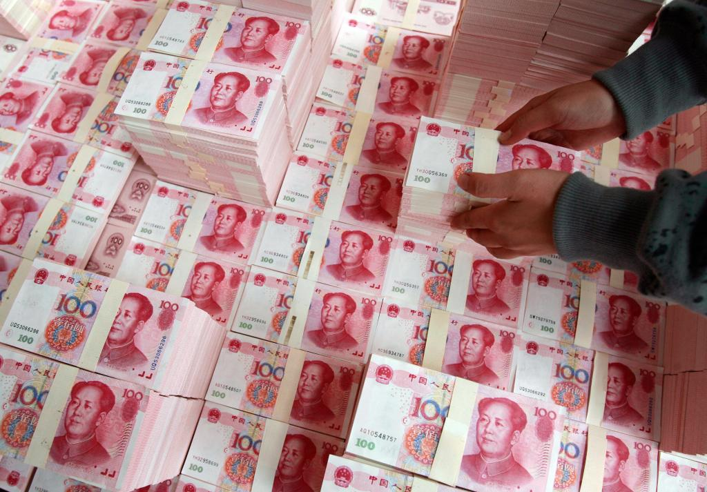 Picture taken 13 October 2007, shows a Chinese artist using Chinese yuan notes to creates a model of Beijing's Central Business District (CBD). China and the United States warned each other Wednesday that their booming but tense trade relationship was under threat from protectionism, as they began two days of top-level economic talks. AFP PHOTO/TEH ENG KOON (Photo credit should read TEH ENG KOON/AFP/Getty Images)