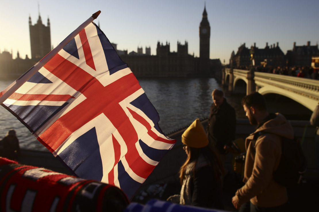 Tourists walk past a souvenir stall selling British Union flags beside Westminster Bridge on the River Thames in view of the Houses of Parliament in London, U.K., on Thursday, Dec. 29, 2016. Demand for luxury brands in the U.K. is flourishing, boosted by increased tourism and spending linked to the weaker pound. Photographer: Simon Dawson/Bloomberg